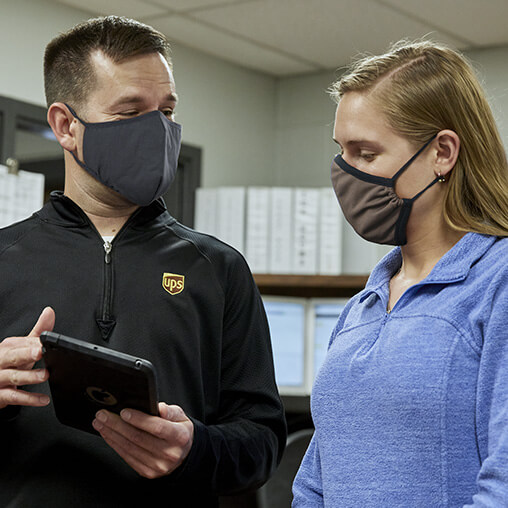 A man and woman are talking while wearing face masks