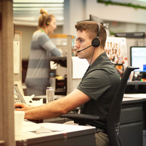 Employee talking, while wearing a telephone headset.