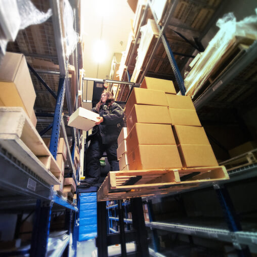 Employee in a warehouse getting boxes.