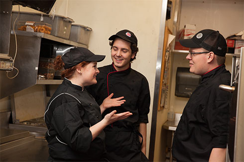 Two cooks talking with kitchen manager