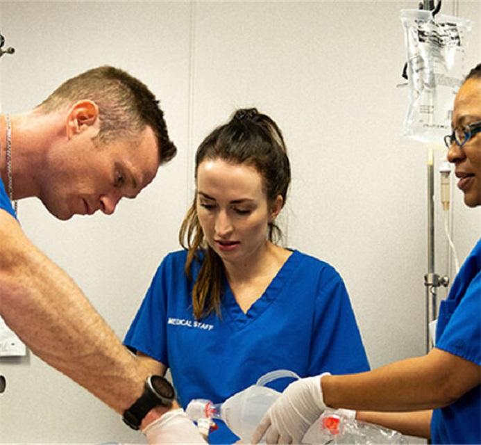 Three people performing medical procedure