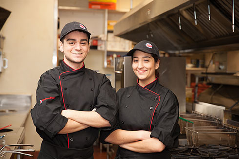 Two cooks smiling for a picture