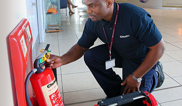 Employee inspecting a fire extinguisher