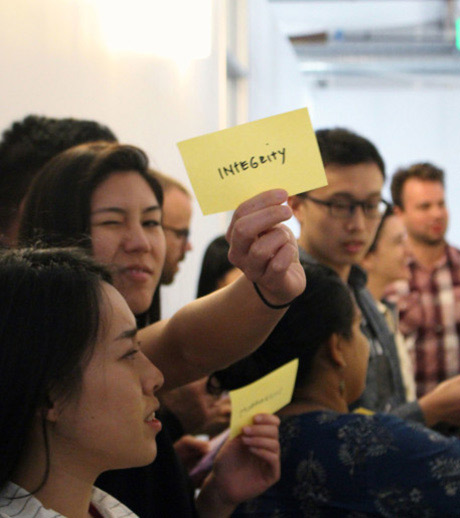 A group of employees, some holding post-it-notes, one note says 'Integrity' on it.