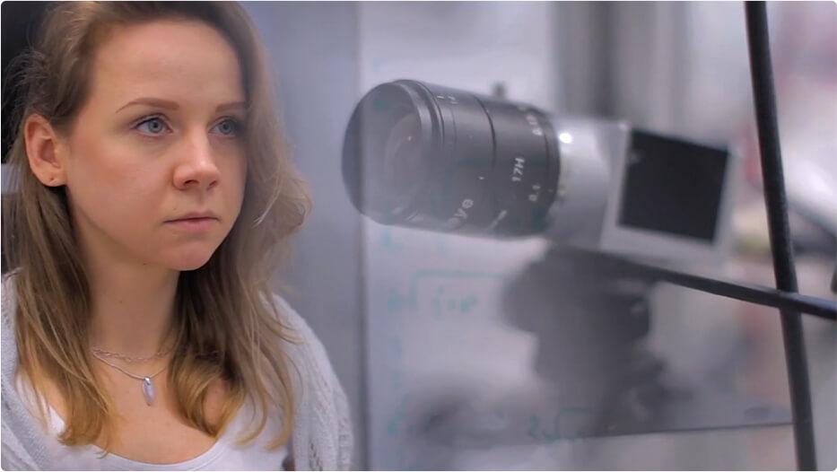 Woman standing beside a camera lens