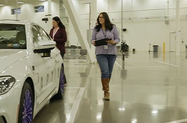 A woman with a clipboard doing and inspection of a vehicle with the APTIV logo on it