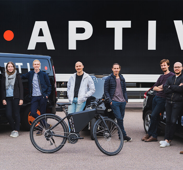 Group of Aptiv Employees standing outside in front of some vehicles