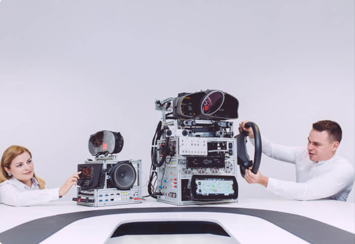 Man and woman working on disconnected vehicle hardware