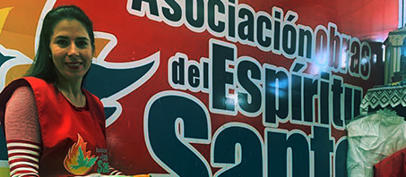 Woman smiling standing in front of a banner with spanish text