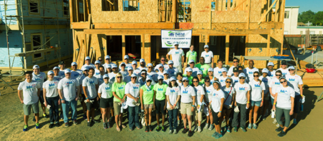 Group of volunteers posing for photo holding Habitat for Humanity sign