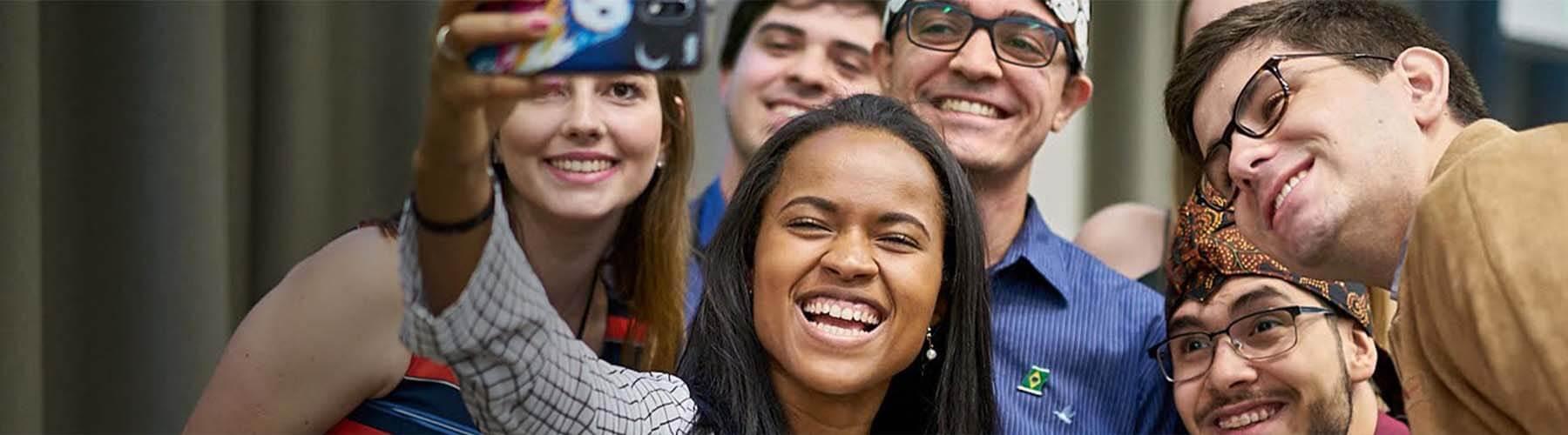 Um grupo de amigos , sorrindo e posando para uma selfie tirada por  mulher negra que está no centro do grupo