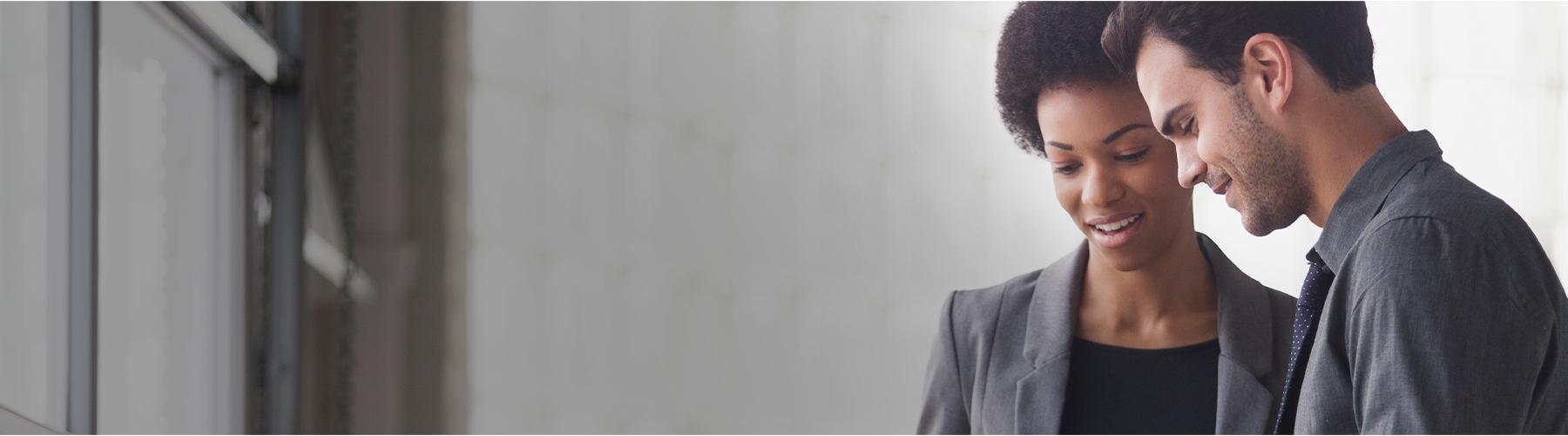Una mujer afroamericana y un hombre caucásico parados juntos, sonriendo. La mujer viste una chamarra gris y el hombre viste una camisa gris con botones y una corbata azul.