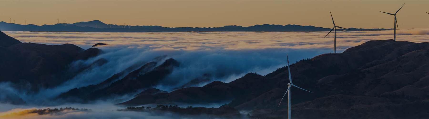 Colinas cubiertas de nubes y niebla. Varias turbinas eólicas dispersas por las colinas.