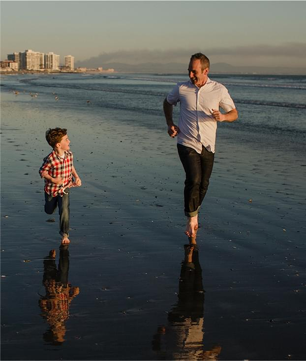 Father running on the beach with his son