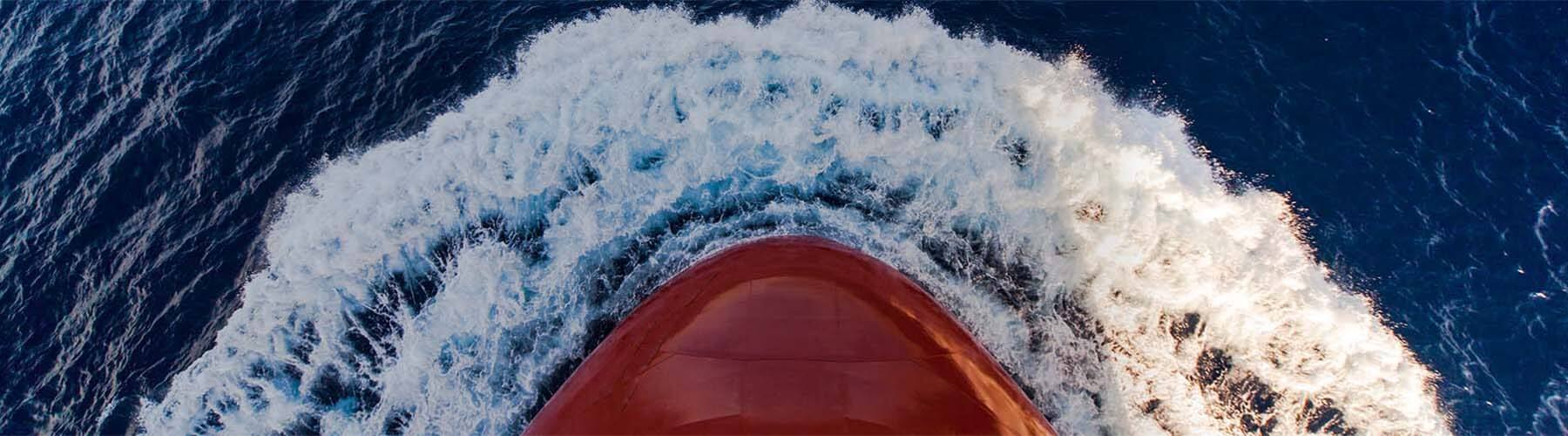 The stern of a shipping vessel, creating a wake as it moves through the ocean.