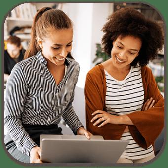 duas mulheres olhando para um laptop