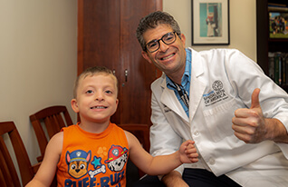 doctor and patient making thumbs up sign with hands