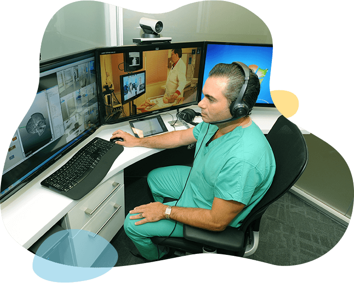 Man with headset sitting infront of computer screens