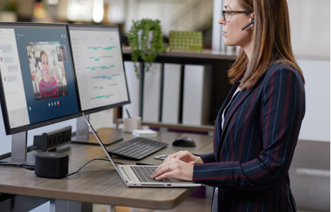 A woman working at a standing deskop on a computer