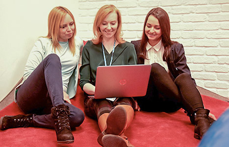 A group of women working together on a laptop