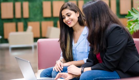 two women viewing a laptop