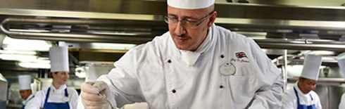 Disney Cruise Line chef putting the finishing culinary touches on a dish
