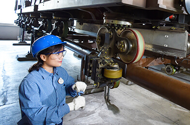 A female with a hard hat and safety glasses using large machinery