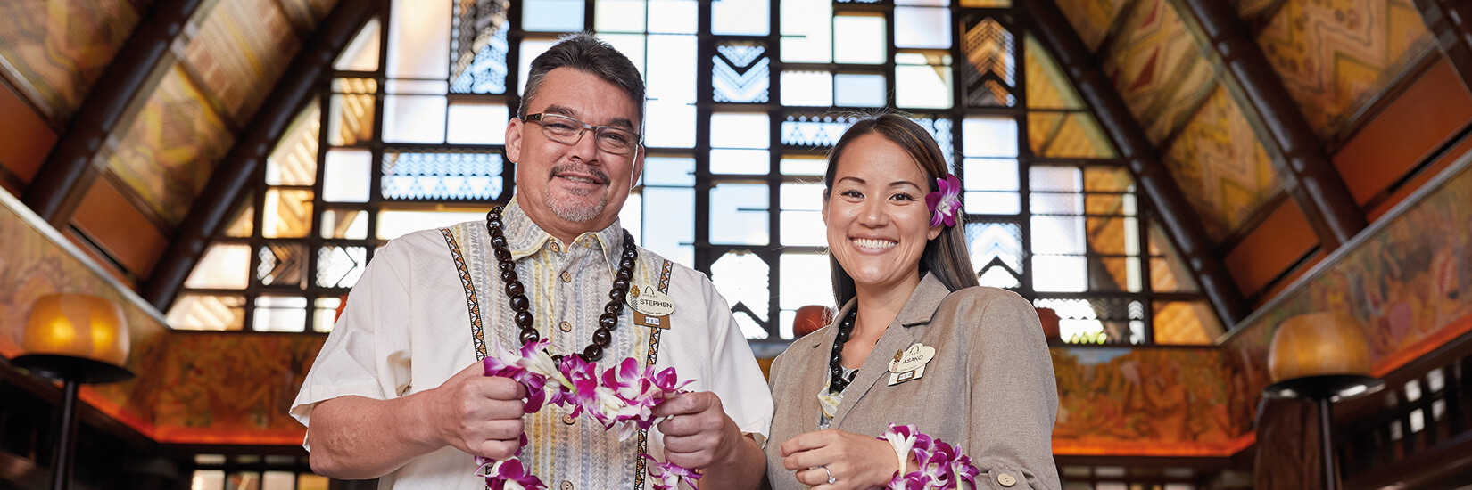Man and woman smiling and holding leis