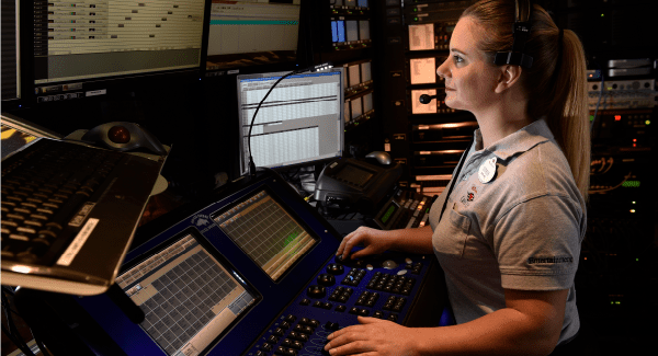 A female staff member wearing a headset at a control terminal with several monitors and switches Eall around her