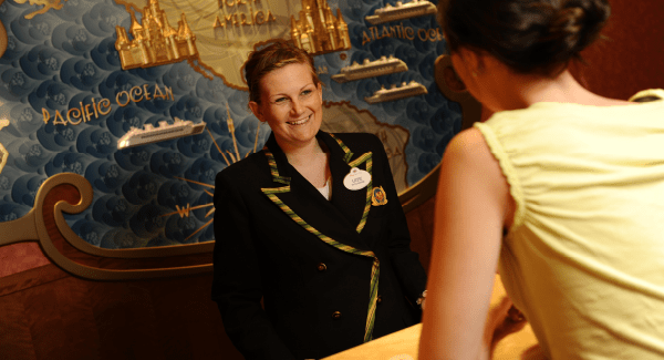 Female staff member in uniform standing behind a reception desk smiling at a customer