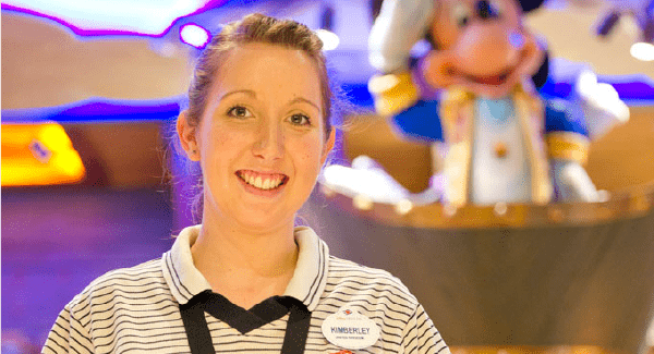 Female staff member smiling in the gift shop in front of a Mickey Mouse display