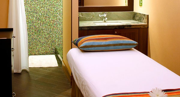 Image of a massage table and pillow in a room with a shower and basin in the background