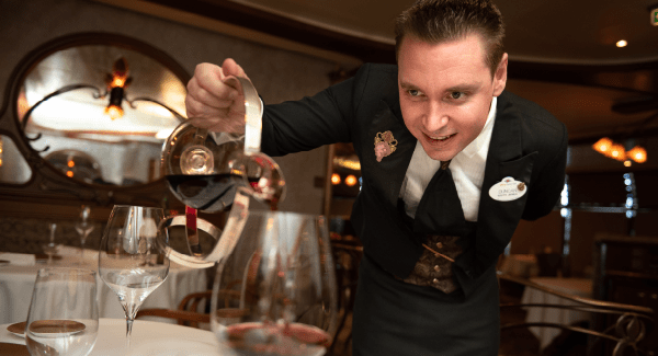 Smartly dressed male waiter pouring wine into a glass