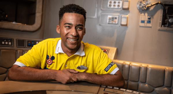 Male employee wearing a yellow shirt Youth Team uniform
