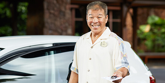 A man who appears to be a valet, smiling and handing over car keys.