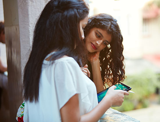 Woman showing another woman something on her phone