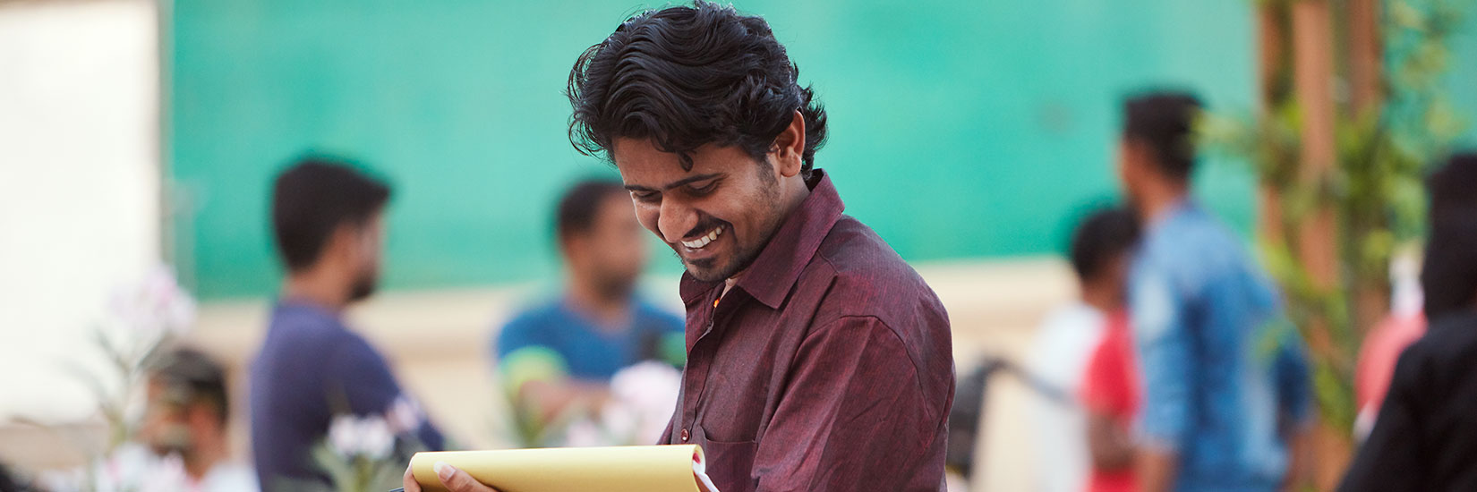 Man looking at pad of paper and smiling