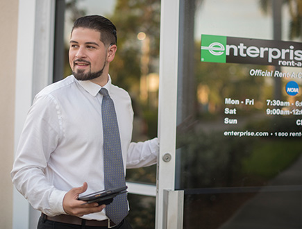 Andres holding open the door to an Enterprise location
