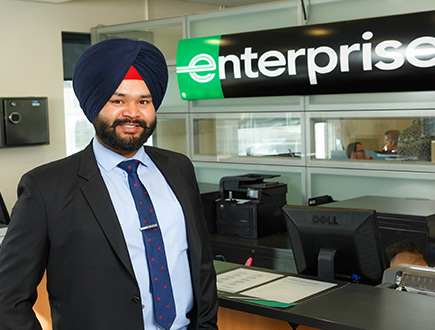 Manmeet standing by welcome desk