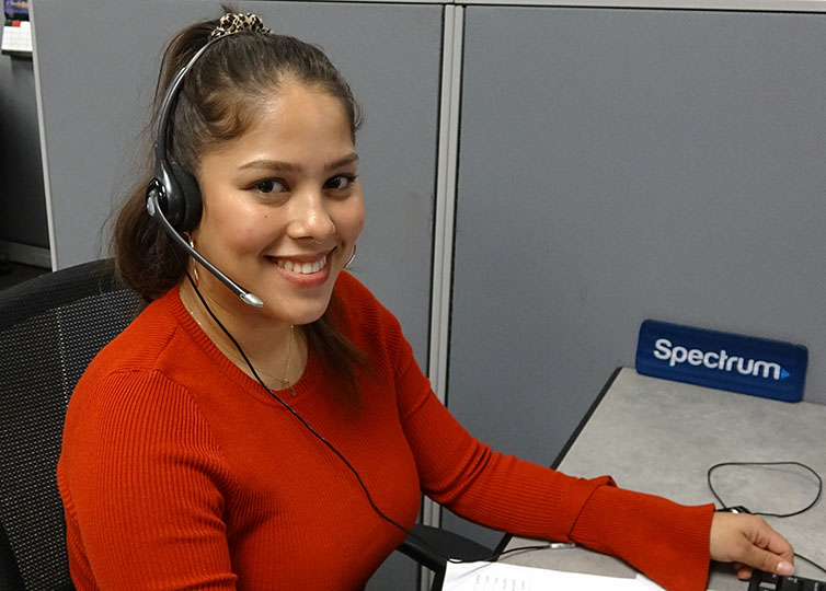 A female Spectrum Call Center Representative in a red sweater wearing a telephone headset