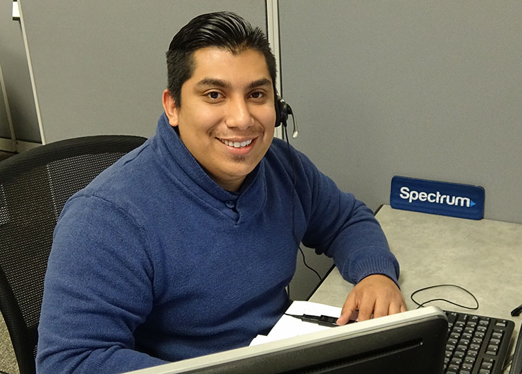 Male Spectrum Call Center Representative in a blue sweater wearing a telephone headset