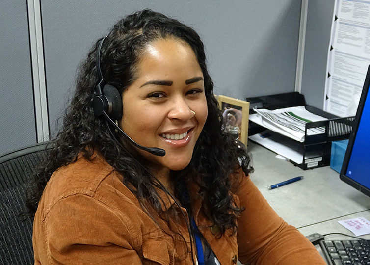 Female Spectrum Call Center Representative wearing a tan jacket wearing a telephone headset