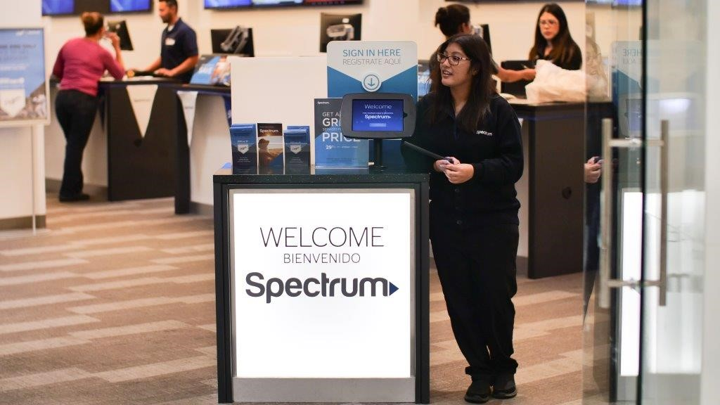 Girl standing next to Spectrum sign