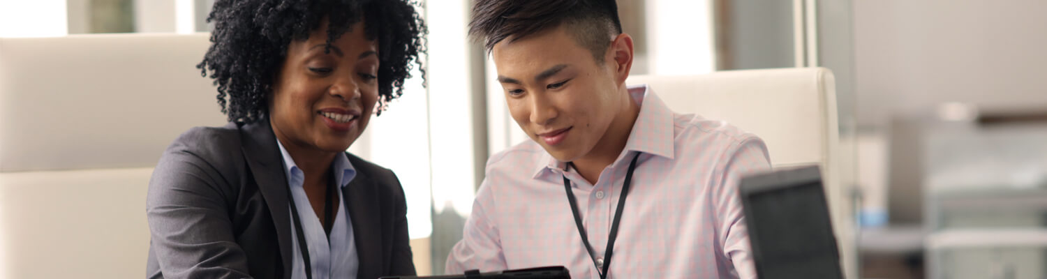 Two employees smiling while looking at a computer screen.