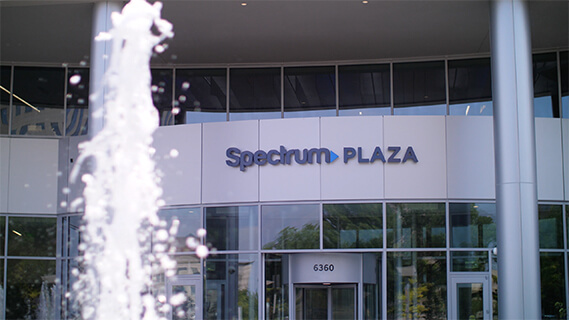 Image of exterior front entrance of Spectrum Plaza building showing a water fountain feature and contemporary architecture