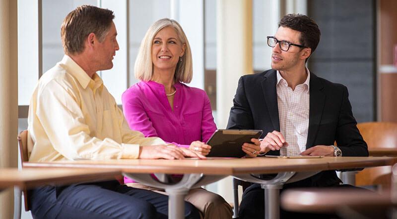 Employees sitting at desk conversing