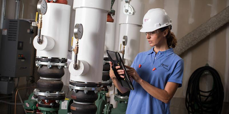 Female engineer inspecting machine using iPad technology