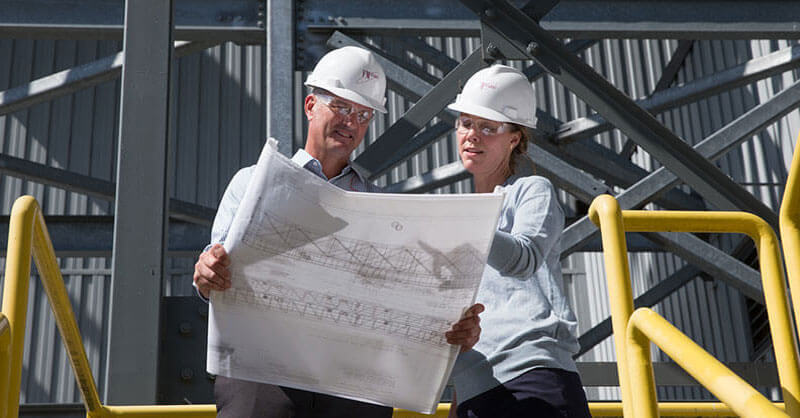 Male and female engineer looking at plans