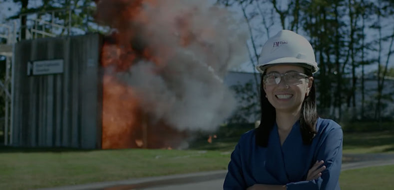 Female engineer smiling in front of burning structure