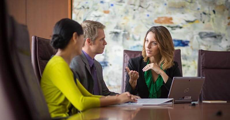 One employee discussing with two clients their investment options
